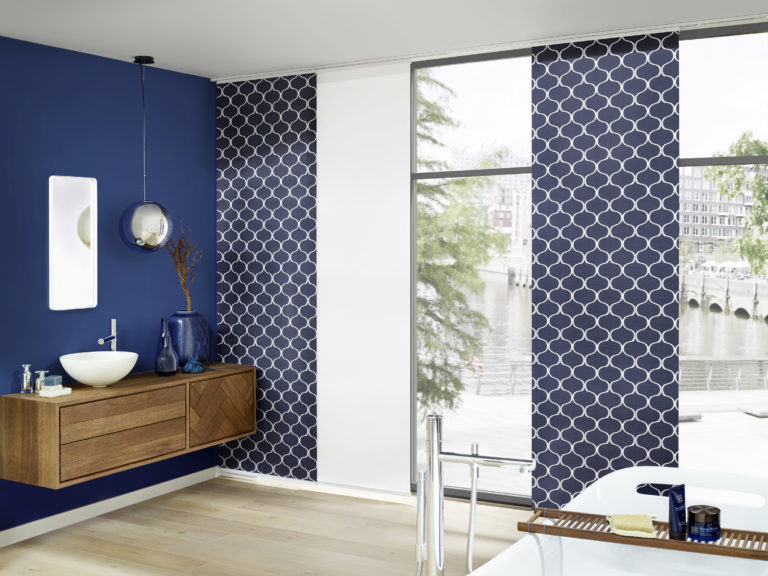 Schönes, modernes großzügiges Bad mit Flächenvorhängen in weiß und blau gemustert mit Blick in die Großstadt, Badewanne und Waschtisch, Vasen und Dekoration