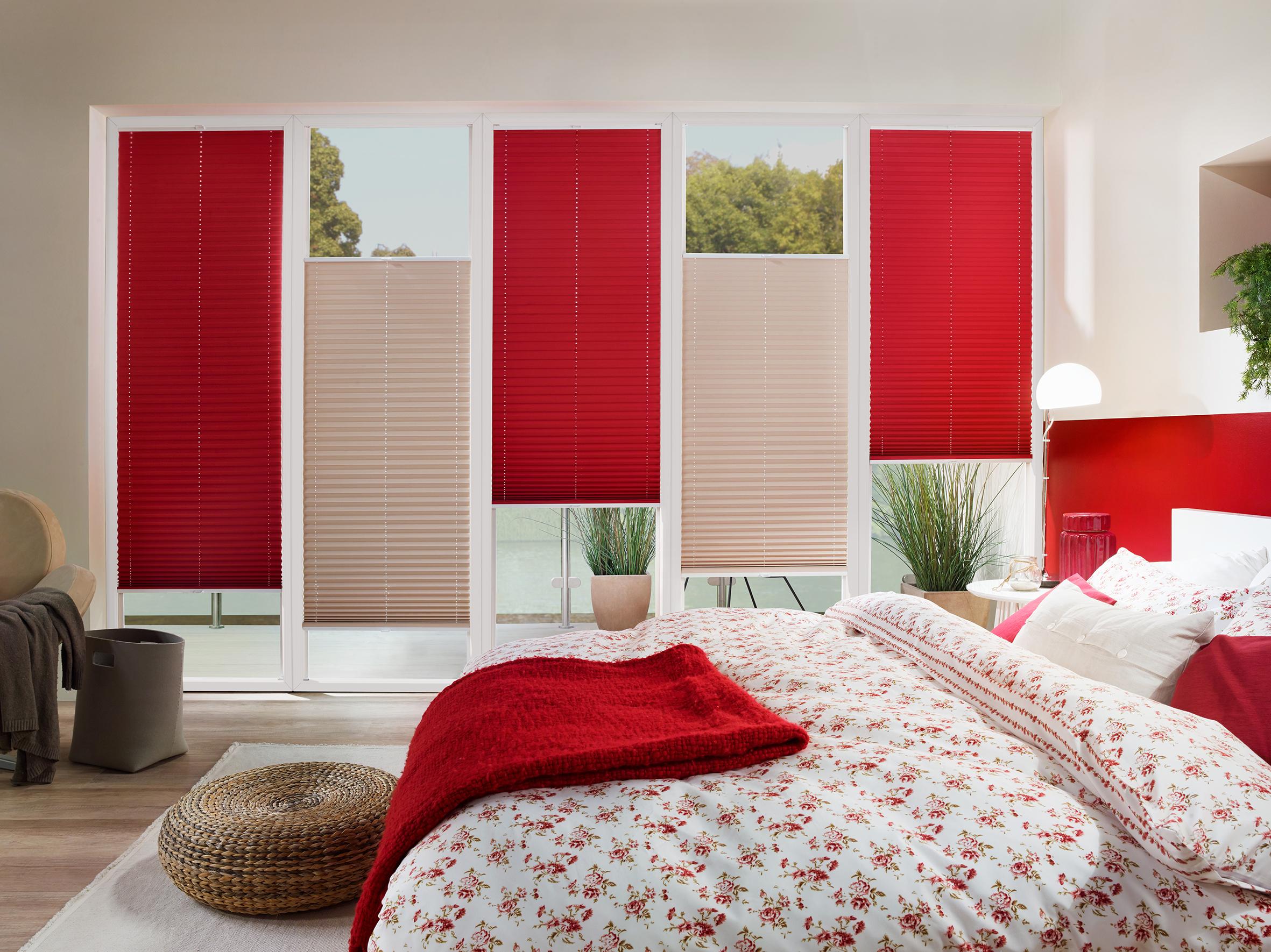 Schlafzimmer mit Plissees in Rot und Blick in den Garten