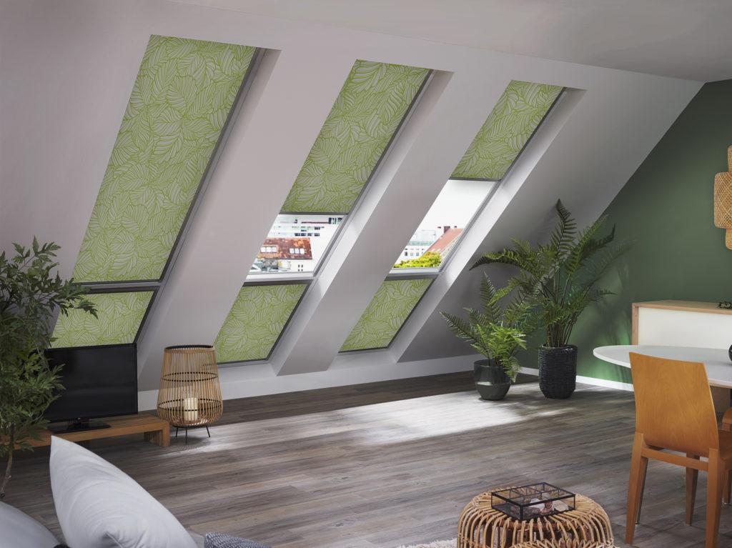 Wohnzimmer mit Esstisch unterm Dach mit Ausblick auf die Stadt und gemusterter Rollo Verdunklungsanlage in grün, Couch mit Couchtisch und Teppich, Esstisch und Stühlen, Sideboard und TV